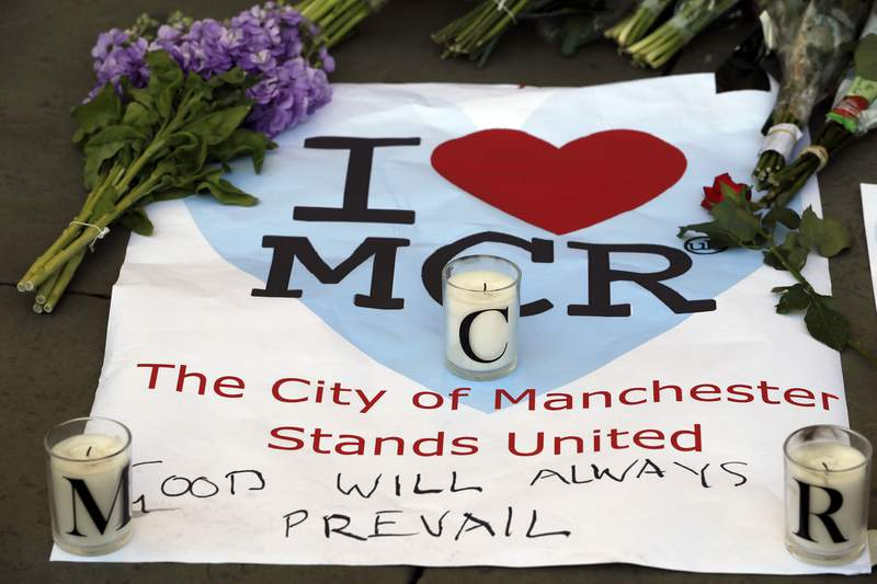 """FILE - In this Tuesday May 23, 2017 file photo, a sign with flowers and candles are placed after a vigil in Albert Square, Manchester, England, the day after the suicide attack at an Ariana Grande concert that left 22 people dead. A public inquiry into a mass attack at a 2017 Ariana Grade concert in northwest England concluded Thursday June 17, 2021, that serious shortcomings by venue operators, security staff and police helped a suicide bomber who killed 22 people carry out his evil intentions."""" (AP Photo/Kirsty Wigglesworth, File)"""