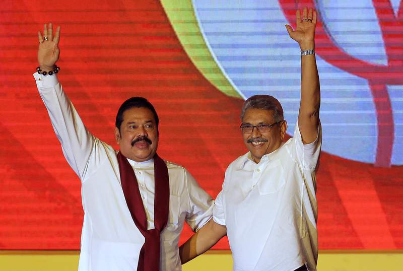 FILE - In this Aug. 11, 2019, file photo, former Sri Lankan President Mahinda Rajapaksa, left, and former Defense Secretary and his brother Gotabaya Rajapaksa wave to supporters during a party convention held to announce the presidential candidacy in Colombo, Sri Lanka. Sri Lankas powerful Rajapaksa brothers secured a landslide victory in the parliamentary election, giving them nearly the two-thirds majority of seats required to make constitutional changes, according to results released Friday, Aug. 7, 2020. Prime Minister Mahinda Rajapaksa is likely to be sworn in the same position by his younger brother, President Gotabaya Rajapaksa, after the vote that could strengthen dynastic rule in the Indian Ocean island nation. (AP Photo/Eranga Jayawardena, File)