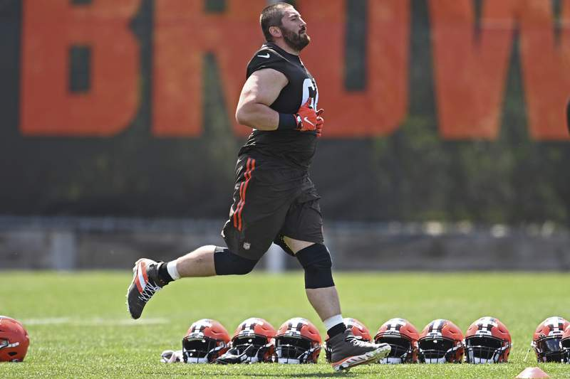 """FILE - Cleveland Browns offensive lineman JC Tretter runs during an NFL football practice at the team training facility in Berea, Ohio, in this Tuesday, June 15, 2021, file photo. Tretter is president of the NFLPA. I know we have learned to work in a very difficult environment, and we will do it again,"""" NFL commissioner Roger Goodell said. """"That is one of the things we learned ... hearing clubs and the NFLPA saying our relationship has never been stronger. I interpret that as a trust that has been built here that will take us forward and will be the long-lasting legacy of this season. (AP Photo/David Dermer, File)"""