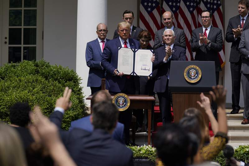 FILE - In this June 5, 2020 file photo, President Donald Trump poses for a photo after signing the Paycheck Protection Program Flexibility Act during a news conference in the Rose Garden of the White House in Washington.  Thousands of minority-owned small businesses were at the end of the line in the governments coronavirus relief program as many struggled to find banks to accept their applications. Or, they were disadvantaged by the program's terms. Data from the Paycheck Protection Program analyzed by The Associated Press show many minority owners desperate for a loan didnt receive one until the PPP's last weeks.   (AP Photo/Evan Vucci, File)