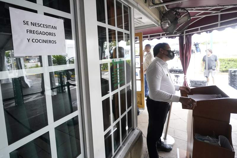 A host stands near a sign written in Spanish looking for dishwashers and cooks, Wednesday, July 14, 2021, in front of the Versailles Cuban restaurant in the Little Havana neighborhood of Miami.  Growth in the services sector, where most Americans work, slowed in August after setting a record pace in July. The Institute for Supply Management reported Friday, Sept. 3 that its monthly survey of service industries decreased to a reading of 61.7 in August after hitting a record high of 64.1 in July.  (AP Photo/Wilfredo Lee)
