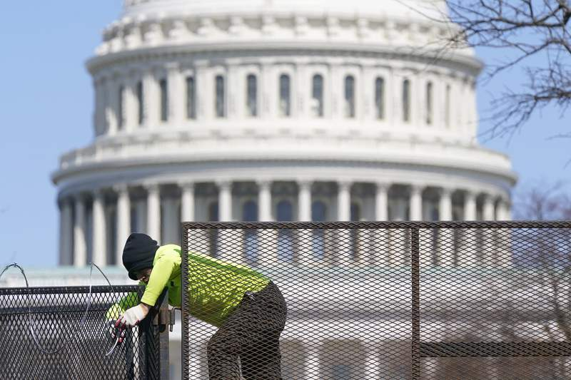 A worker removes razor wire from a security fence on Capitol Hill in Washington, Saturday, March 20, 2021. (AP Photo/Patrick Semansky)