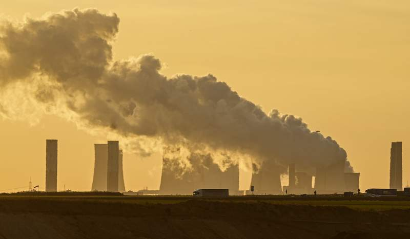 FILE - In this Oct. 1, 2021, file photo, a power plant fires coal from the nearby Garzweiler open-cast mine near Luetzerath, western Germany. Dozens of large German companies have urged the country's next government to put in place ambitious policies to meet the goals of the Paris climate accord. (AP Photo/Martin Meissner, File)