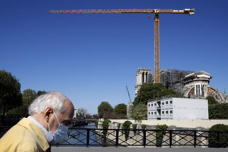 FILE  - In this Tuesday, April 14, 2020 file photo, a man wearing face mask walks past Notre Dame Cathedral in Paris. Officials say restorers at Paris fire-damaged Notre Dame cathedral have completed key preliminary work by successfully removing all the perilous roof scaffolding. It was thought that the scaffolding might have melded to the cathedral in the fire, and be keeping it in place. When the Notre Dame fire broke out on April 15 last year destroying the spire, the cathedral was already under restoration. The scaffolding previously installed resisted collapse, but was deformed by the heat of the fire Notre Dame restoration officials said in a communique. (AP Photo/Christophe Ena, File)