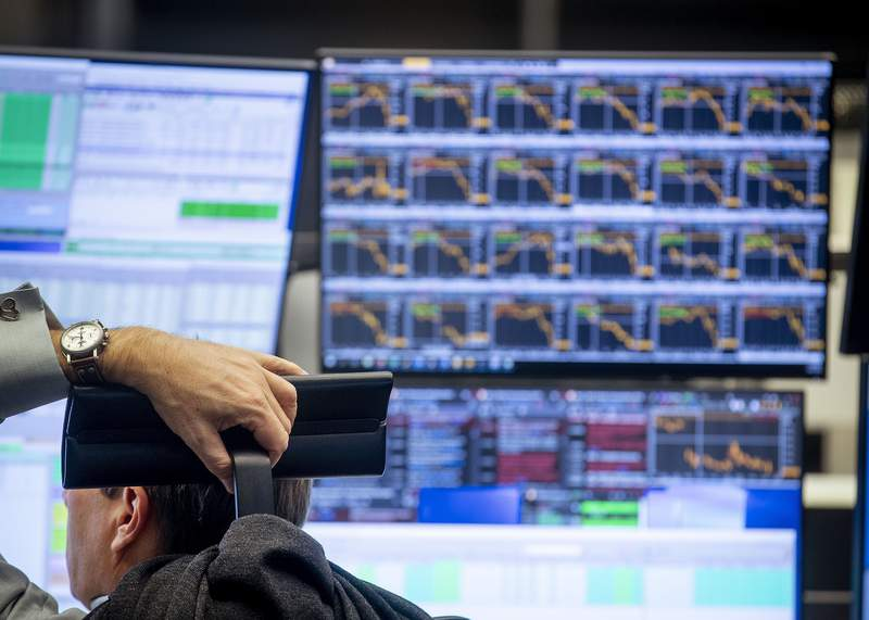 A broker watches his screens at the stock market in Frankfurt, Germany, Friday, March 13, 2020. For most people, the new coronavirus causes only mild or moderate symptoms, such as fever and cough. For some, especially older adults and people with existing health problems, it can cause more severe illness, including pneumonia. (AP Photo/Michael Probst)