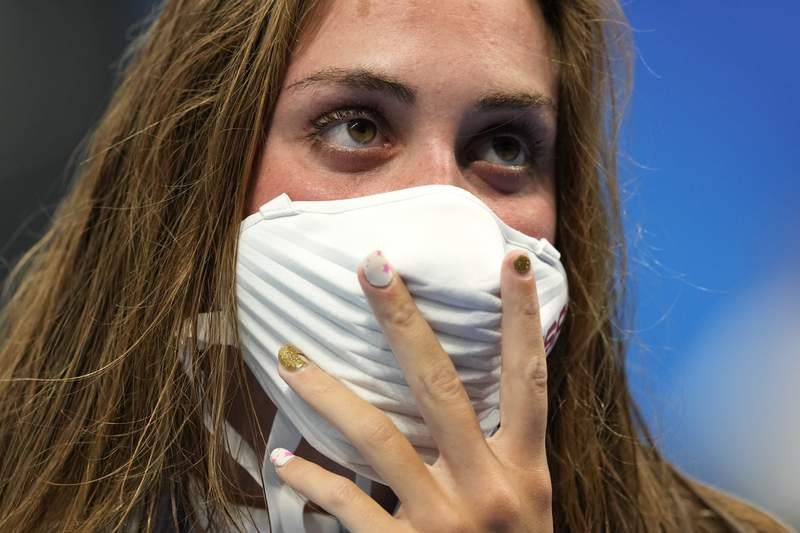 Silver medalist Emma Weyant, of United States, holds her mask during the medal ceremony for the women's 400-meter Individual medle at the 2020 Summer Olympics, Sunday, July 25, 2021, in Tokyo, Japan. (AP Photo/Martin Meissner)