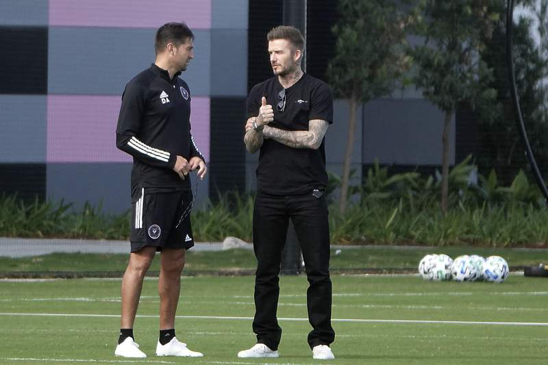 InterMiami co-owner David Beckham, right, talks with head coach Diego Alonso during an MLS training session, Thursday, March 12, 2020, in Fort Lauderdale, Fla.  Major League Soccer is shutting down for 30 days because of the coronavirus, delaying the home opener for the expansion InterMiami team co-owned by former England captain David Beckham. The vast majority of people recover from the new coronavirus. According to the World Health Organization, most people recover in about two to six weeks, depending on the severity of the illness. (Joe Cavaretta/South Florida Sun-Sentinel via AP)