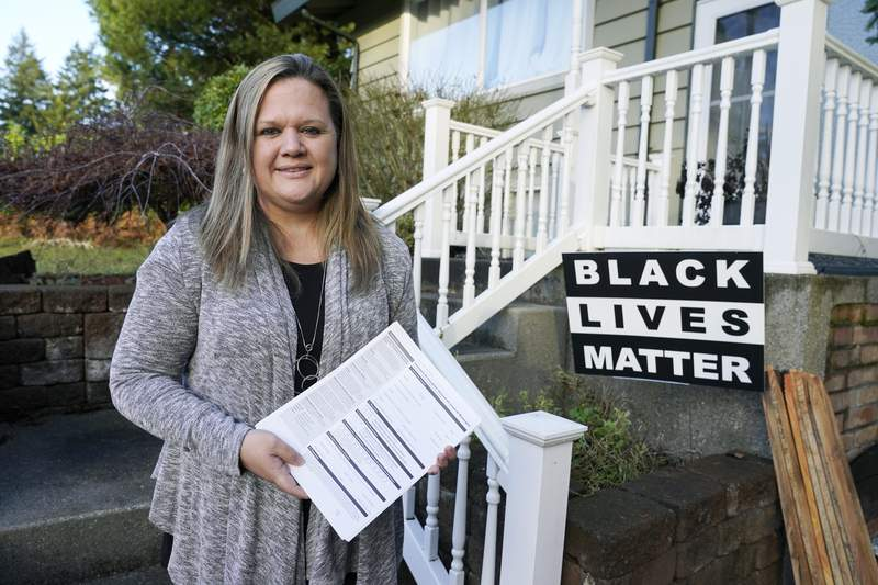 """FILE - In this Dec. 9, 2020, file photo, state Rep. Tarra Simmons, D-Bremerton, holds blank voter registration forms as she poses for a photo at her home in Bremerton, Wash. Washington state lawmakers have voted to automatically restore voting rights to people who have been released from prison after committing felonies, even if they're still on community supervision. Simmons of Bremerton, who was incarcerated herself before being released and becoming a lawyer. """"Her success story is what we want for all people who are completing their prison term,"""" Sen. Patty Kuderer, D-Bellevue, said during the floor debate. """"Let's give that opportunity to others as well by restoring their voices and their right to vote."""" (AP Photo/Ted S. Warren, File)"""