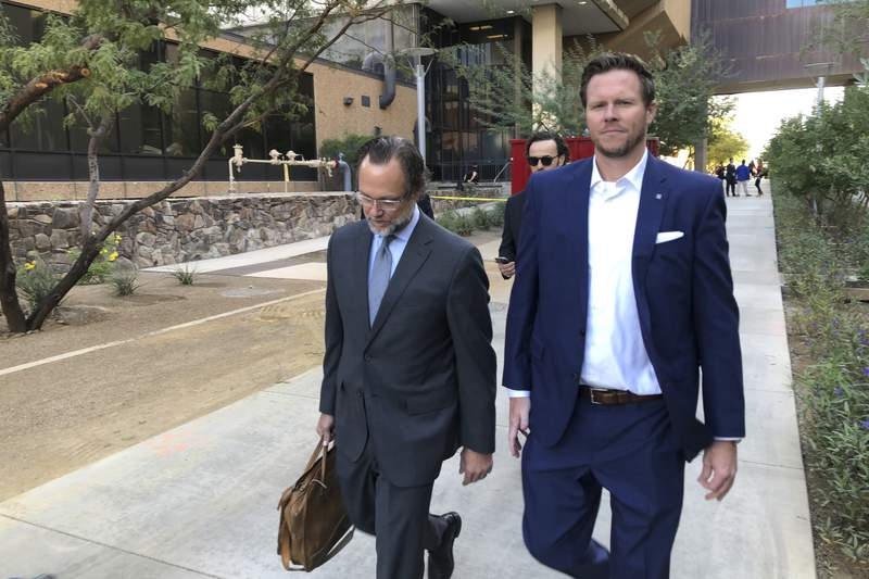 FILE - In this Nov. 5, 2019, file photo, then-Maricopa County Assessor Paul Petersen, right, and his attorney, Kurt Altman, leave a court hearing in Phoenix. Petersen is scheduled on Friday, March 19, 2021, to receive the second of three prison sentences for convictions stemming from his acknowledged operation of an illegal adoption scheme involving women from the Marshall Islands. (AP Photo/Jacques Billeaud, File)