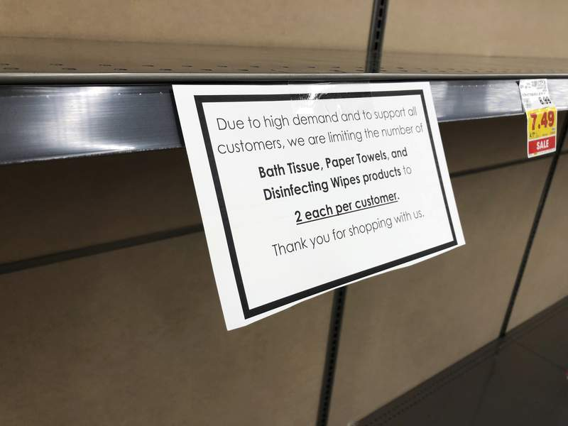 FILE - In this Wednesday, Nov. 4, 2020, file photo, a sign advising of the limit on purchases of paper products hangs on an empty shelf in a grocery store in southeast Denver. Stores are starting to look like they did this spring when the coronavirus pandemic started, with bare shelves and limits on what you can buy. (AP Photo/David Zalubowski, File)