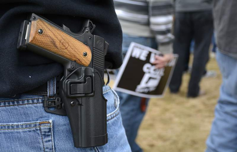 """FILE - In this April 5, 2014, file photo, a man open carries a 1911 handgun while at a CCDL gun rights rally at the Connecticut state capitol in Hartford. The Democratic co-chairmen of the Judiciary Committee, Sen. Gary Winfield and Rep. Steve Stafstrom, have introduced a bill to revamp Connecticut's 1999 """"red flag"""" law, which was the first in the country to allow judges to order someone's guns seized upon evidence they are a danger to themselves or others. The bill would add relatives, household members and medical professionals, including physicians, physician assistants, nurses and psychologists. (Mike Orazzi/The Bristol Press via AP, File)"""