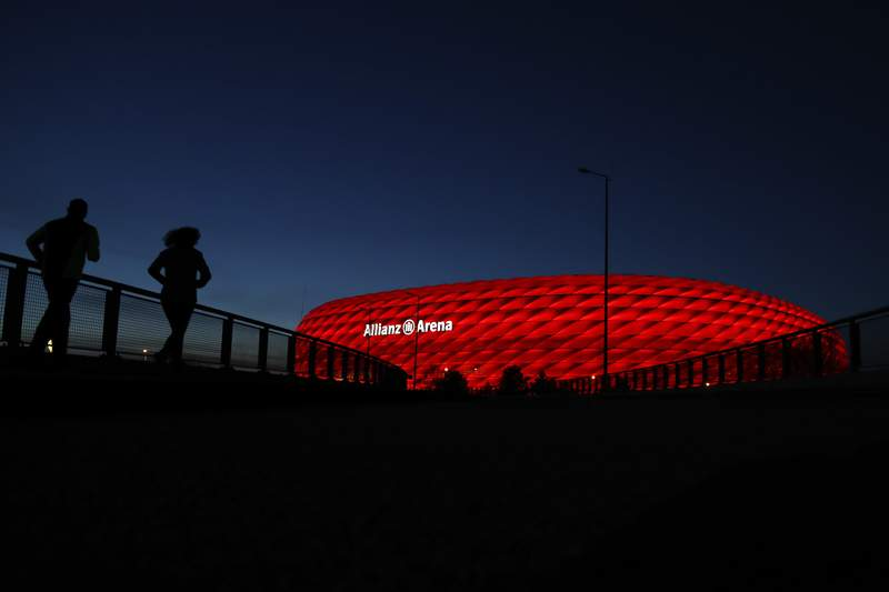 FILE-In this March 16, 2020 taken photo jogger make their way after the sun sets at the 'Allianz Arena' soccer stadium in Munich, Germany. European ruling body UEFA said on Friday the German city of Munich will remain as one of the Euro 2020 host cities. The confirmation came during a UEFA executive board videoconference after the federation was informed by local authorities that all four matches in Munich will be able to welcome a minimum of 14,500 spectators. (AP Photo/Matthias Schrader)