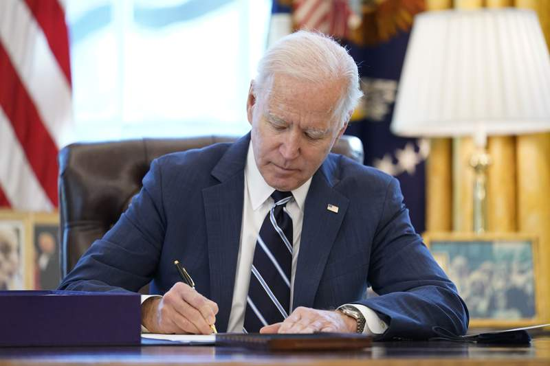 President Joe Biden signs the American Rescue Plan, a coronavirus relief package, in the Oval Office of the White House, Thursday, March 11, 2021, in Washington. (AP Photo/Andrew Harnik)