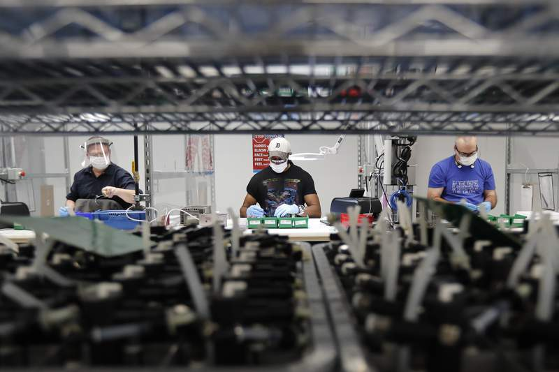 FILE - In this May 13, 2020, file photo, Ford Motor Co., line workers put together ventilators that the automaker is assembling at the Ford Rawsonville plant in Ypsilanti Township, Mich. U.S. industrial production increased 0.4% in November with manufacturing receiving a boost from a rebound in output at auto plants after three months of declines. The Federal Reserve reported Tuesday, Dec. 15 that the November gain in industrial output followed an even stronger 0.9% increase in October. (AP Photo/Carlos Osorio, File)