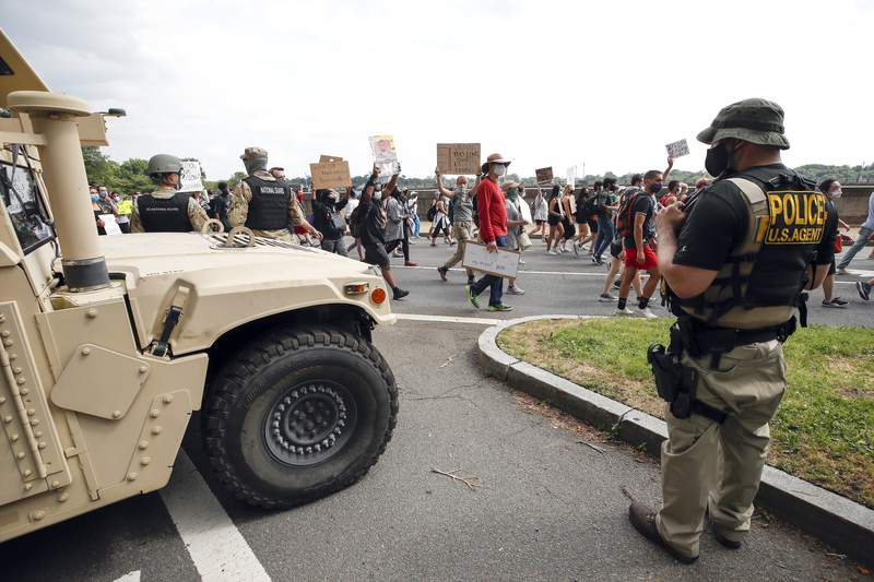DC National Guard soldiers and other law enforcement personnel watch as demonstrators protest Saturday, June 6, 2020, along Independence Avenue in Washington, over the death of George Floyd, a black man who was in police custody in Minneapolis. Floyd died after being restrained by Minneapolis police officers. (AP Photo/Alex Brandon)
