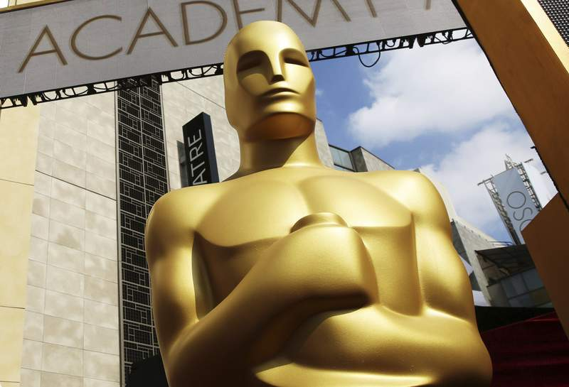 FILE - In this Feb. 21, 2015 file photo, an Oscar statue appears outside the Dolby Theatre for the 87th Academy Awards in Los Angeles. The Academy of Motion Picture Arts and Sciences laid out sweeping eligibility reforms to the best picture category intended to encourage diversity and equitable representation on and off screen beginning with the 96th Academy Awards. The announcement on Sept. 8, 2020, became a hotly debated topic on social media with some claiming it goes too far and others saying it doesn't go far enough. (Photo by Matt Sayles/Invision/AP, File)