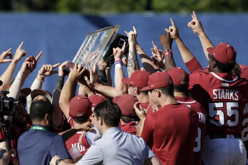 Arkansas players hoist the championship trophy after defeating Tennessee in an NCAA college baseball championship game during the Southeastern Conference tournament Sunday, May 30, 2021, in Hoover, Ala. (AP Photo/Butch Dill)