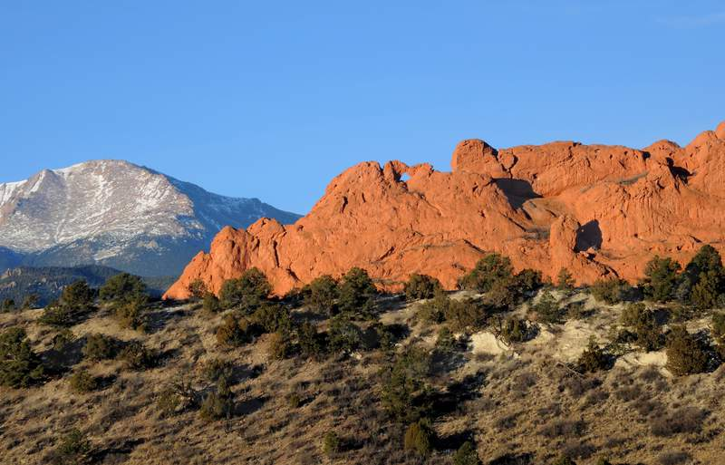 COLORADO SPRINGS, CO - DECEMBER 27, 2013: Sandstone formations rise near the entrance to the Garden of the Gods park in Colorado Springs, Colorado. The National Natural Landmark features imposing red sandstone rock formations created during a geological upheaval millions of years ago. Snow-covered Pike's Peak is in the background. (Photo by Robert Alexander/Getty Images)