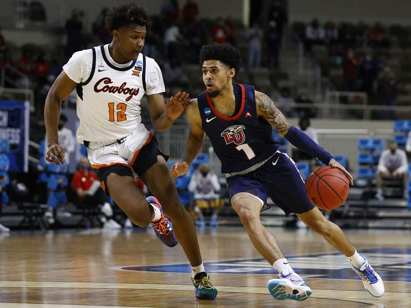 INDIANAPOLIS, INDIANA - MARCH 19: Chris Parker #1 of the Liberty Flames drives past Matthew-Alexander Moncrieffe #12 of the Oklahoma State Cowboys during the first half in the first round game of the 2021 NCAA Men's Basketball Tournament at Indiana Farmers Coliseum on March 19, 2021 in Indianapolis, Indiana. (Photo by Maddie Meyer/Getty Images)