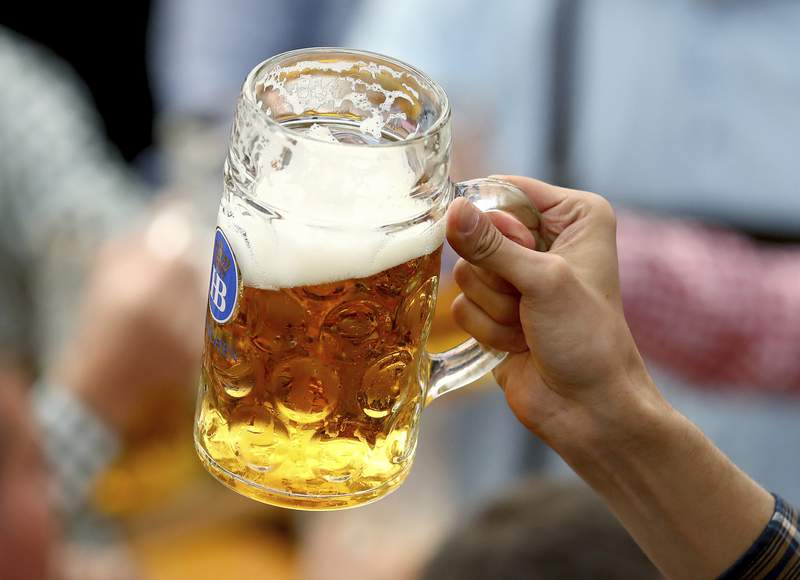FILE - In this Sept.21, 2019 file photo a guest holds glasses of beer during the opening of the 186th 'Oktoberfest' beer festival in Munich, Germany. German beer sales in this years first half were 2.7% lower than a year earlier. They were dragged lower by closures of bars and restaurants that stretched through winter and into spring. (AP Photo/Matthias Schrader, file)