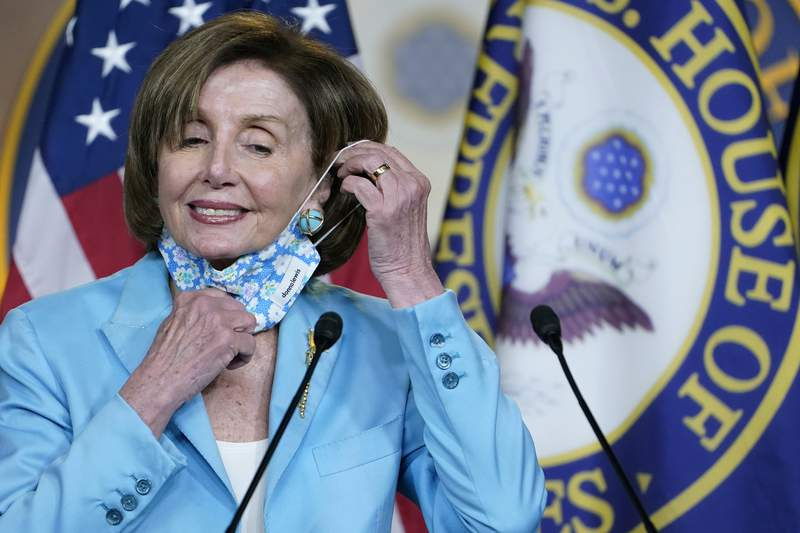 FILE - In this May 19, 2021, file photo House Speaker Nancy Pelosi of Calif., takes off her face mask to talk to reporters on Capitol Hill in Washington. Fully vaccinated members of Congress and their staff will no longer have to wear a mask on the House floor and in committee rooms, according to guidance issued Friday, June 11, by the Office of the Attending Physician, delighting some GOP lawmakers who have been chafing at the mask-wearing requirements in recent months. (AP Photo/Susan Walsh, File)