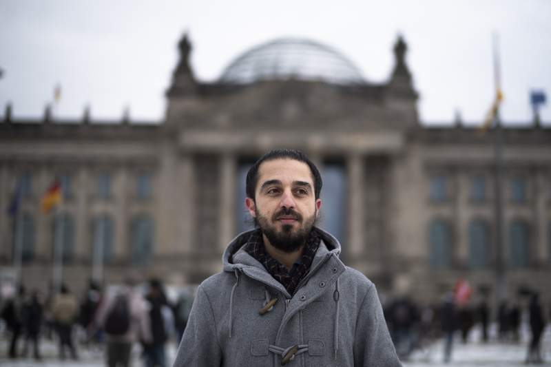 FILE - In this Saturday, Feb. 6, 2021 file photo Tareq Alaows, who is running to become a lawmaker at the German parliament Bundestag poses in front of the Reichstag building in Berlin, Germany. Tareq Alaows who came to Germany as an asylum-seeker in 2015 and launched his campaign to run in Germany's federal election in September for the Green Party said in a statement Tuesday that he had decided to no longer run for parliament for personal reasons. (AP Photo/Markus Schreiber, file)