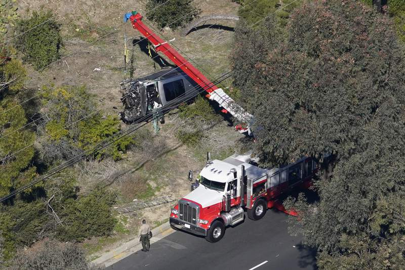 Workers move a vehicle after a rollover accident involving golfer Tiger Woods Tuesday, Feb. 23, 2021, in the Rancho Palos Verdes section of Los Angeles. Woods suffered leg injuries in the one-car accident and was undergoing surgery, authorities and his manager said. (AP Photo/Mark J. Terrill)
