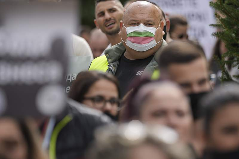 A man wears a mask in the colors of the Bulgarian flag while attending a protest by restaurant workers in Veliko Tarnovo, Bulgaria, Thursday, Sept. 2, 2021. Since the start of the pandemic, more than 19,000 people in Bulgaria have died of COVID-19, a grim statistic that makes the country's death rate from the disease the EU's third-highest behind only the Czech Republic, and Hungary. (AP Photo/Vadim Ghirda)