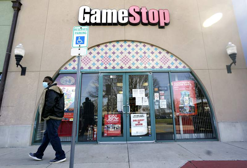 FILE - In this Jan. 28, 2021 file photo, a pedestrian passes a GameStop storefront in Dallas. A hefty tax benefit helped drive GameStops fiscal fourth-quarter profit sharply higher, but the video-game retailers sales declined despite a surge in its online business. The company's latest results fell short of Wall Streets expectations. (AP Photo/LM Otero, File)