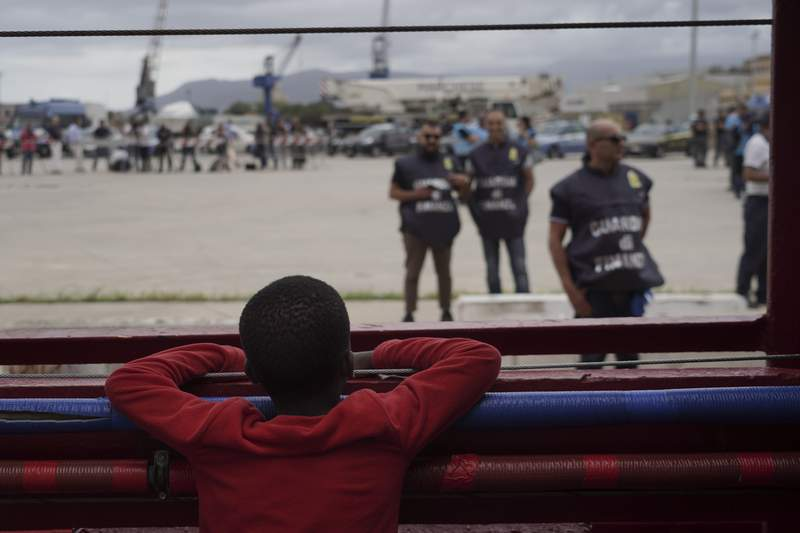 FILE - In this Tuesday, Sept. 24, 2019 file photo, a boy looks at police from aboard the Ocean Viking in the Mediterranean Sea. A France-based migrant rescue organization will be getting assistance aboard its charity ship in the Mediterranean.  The International Federation of Red Cross and Red Crescent Societies, known as IFRC, said on Monday, July 19, 2021 its teams will go aboard the Ocean Viking rescue ship starting in August in the central Mediterranean Sea. That's an area heavily used by traffickers based in Libya who launch unseaworthy boats crowded with migrants toward Italy's southern shores. (AP Photo/Renata Brito, File)