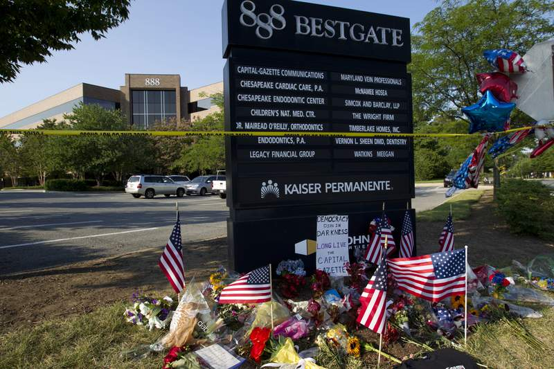 """FILE - In this July 1, 2018 file photo a makeshift memorial is seen at the scene outside the office building housing The Capital Gazette newspaper in Annapolis, Md.   Maryland is set to award $300,000 for the construction of a memorial honoring the victims of the 2018 shooting at the a newspaper office that killed five people. The Capital Gazette reports the state plans to award the funds next week for a memorial called Guardians of Free Speech.""""  (AP Photo/Jose Luis Magana, File)"""