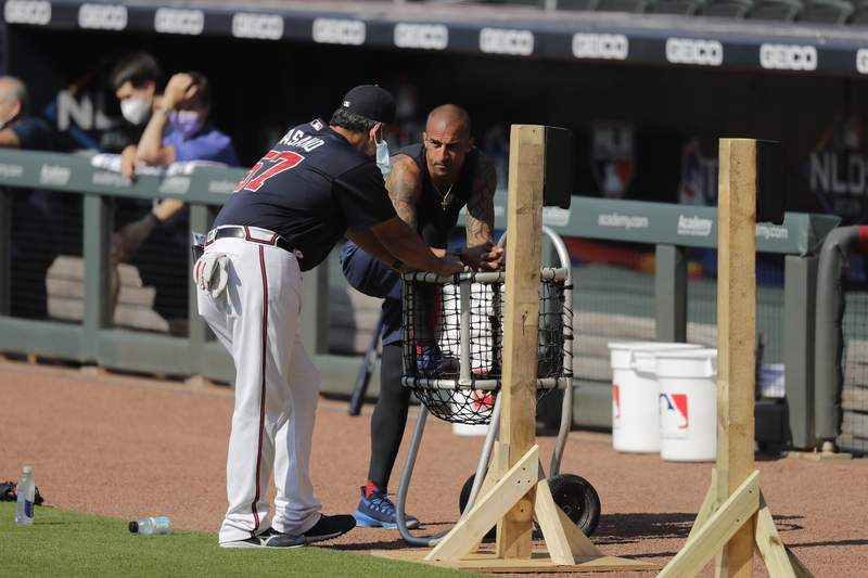 FILE - In this July 5, 2020, file photo, Atlanta Braves' Nick Markakis, right, talks with a coach during team practice at Truist Park in Atlanta. Braves outfielder Nick Markakis has opted out of the 2020 season. The 36-year-old Markakis said he was uneasy about playing the season without fans and then was swayed by his telephone conversation with teammate Freddie Freeman, who has tested positive for COVID-19 and has fever and other symptoms. (AP Photo/Brynn Anderson, File)