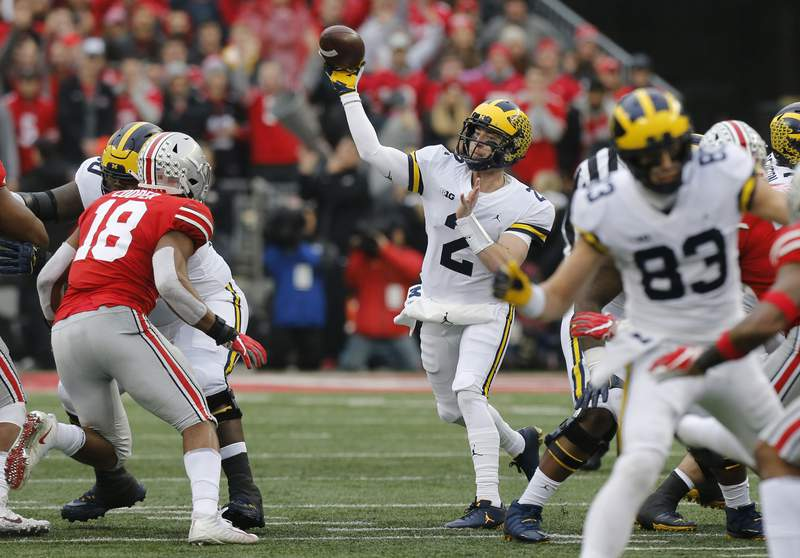 """FILE - In this Nov. 24, 2018, file photo, Michigan quarterback Shea Patterson throws a pass against Ohio State during an NCAA college football game in Columbus, Ohio. Magistrate Judge Norah McCann King moved a change of plea hearing from June 18 to July 1, 2020, for Daniel Rippy. Rippy is accused of making an """"electronic communication"""" threat from California during this game between Ohio State and the University of Michigan threatening a shooting and vowing to hurt players on the football team. (AP Photo/Jay LaPrete)"""