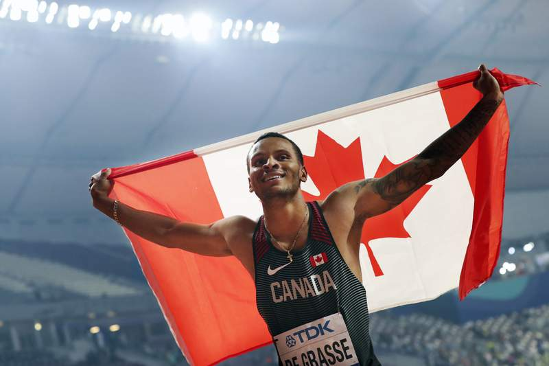 FILE - In this Tuesday, Oct. 1, 2019, file photo, Canada's Andre De Grasse celebrates after winning the silver medal in the men's 200-meters at the World Athletics Championships in Doha, Qatar. Stunned at first, sprinter Andre De Grasse said he understands Team Canada's decision to not send a team to the Tokyo Olympics due to the coronavirus pandemic unless they were delayed a year. (AP Photo/Hassan Ammar, File)