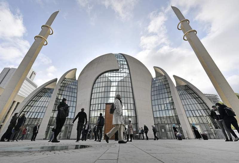 """FILE - In this Oct. 3, 2017 file photo people stand outside the central DITIB mosque on the """"Day of Open Mosques"""" in Cologne. The German city of Cologne will start permitting mosques to broadcast muezzin calls for prayer, the city said on Monday. The calls can be aired via loudspeakers for a time period of five minutes every week for the Friday prayer around noon time. (AP Photo/Martin Meissner, file)"""