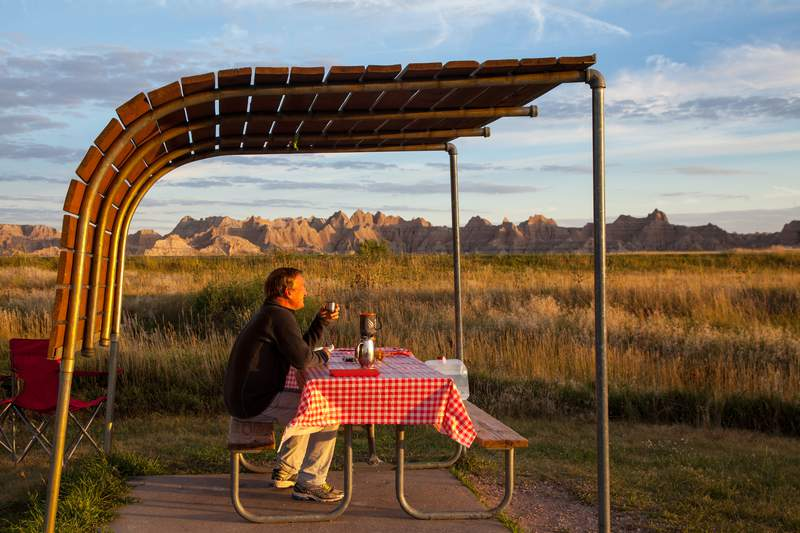 A man having coffee in the early morning hours at a campsite in Badlands National Park, South Dakota.