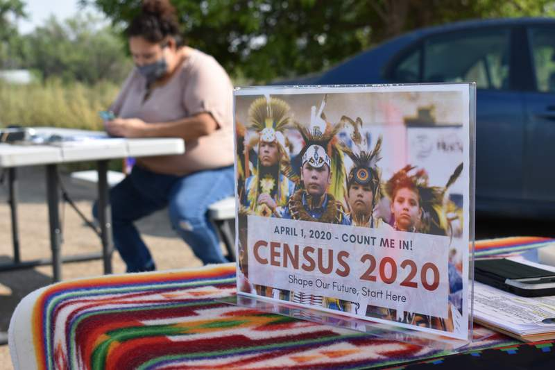 A sign promoting Native American participation in the U.S. census is displayed as Selena Rides Horse enters information into her phone on behalf of a member of the Crow Indian Tribe in Lodge Grass, Mont. on Wednesday, Aug. 26, 2020. There are more than 300 Native American reservations across the country, and almost all lag the rest of the country in participation in the census. (AP Photo/Matthew Brown)