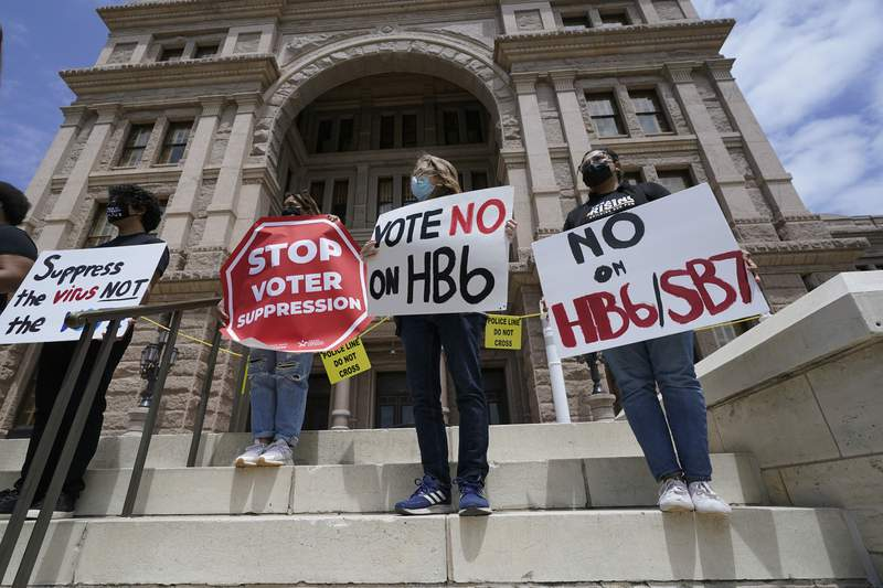 FILE - In this April 21, 2021, file photo, people opposed to Texas voter bills HB6 and SB7 hold signs during a news conference hosted by Texas Rising Action on the steps of the State Capitol in Austin, Texas. Republican lawmakers around the country are pressing ahead with efforts to tighten voting laws, despite growing warnings from business leaders that the measures could harm democracy and the economic climate. (AP Photo/Eric Gay, File)