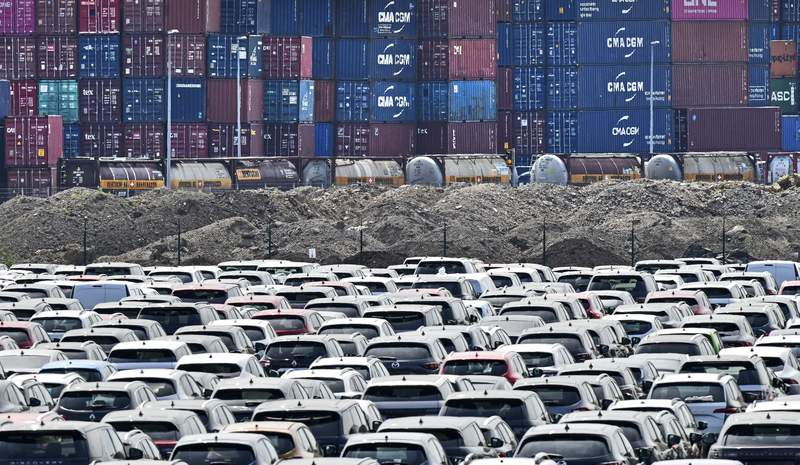 FILE - In this Wednesday, June 3, 2020 photo new cars are stored in front of containers at the 'logport' (logistic port) in Duisburg, Germany.  Official statistics show that the German economy grew 0.3% in last years fourth quarter compared with the previous three-month period  a better performance than first thought. (AP Photo/Martin Meissner, file)