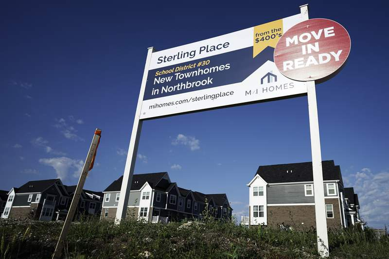 An advertising sign for building land stands in front of a new home construction site in Northbrook, Ill., Wednesday, June 23, 2021.  Average long-term mortgage rates dipped lower this week, Thursday, Sept. 16, as economic prospects continued muted amid a wave of new delta variant coronavirus cases.   (AP Photo/Nam Y. Huh)