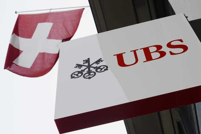 FILE - This April 24, 2014, file photo shows the logo of Swiss bank UBS and the Swiss flag in Zurich, Switzerland. The multinational investment bank has ended support for offshore drilling in the Arctic amid efforts to tackle climate change, a move that could affect future funding for oil and gas projects in Alaska, the Anchorage Daily News reported Friday, March 6, 2020. (Steffen Schmidt/Keystone via AP, File)
