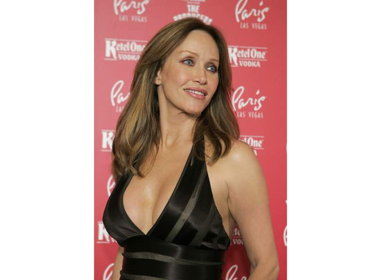 """FILE - Actress Tanya Roberts poses for photos at the grand opening of the musical comedy """"The Producers"""" at the Paris hotel-casino in Las Vegas on Feb. 9, 2007. Roberts, who captivated James Bond in A View to a Kill and later played Midge Pinciotti in the sitcom That 70s Show, has been hospitalized after falling at her home. The actor had mistakenly been reported dead by her publicist Mike Pingel earlier Monday, Jan. 4 2021. Pingel told The Associated Press Monday afternoon that Roberts, 65, is alive but in poor condition. (AP Photo/Jae C. Hong, File)"""