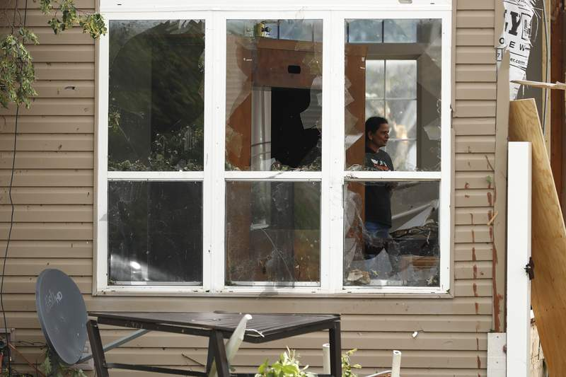 A household member of a damaged house is seen through a broken window after a tornado passed through the area, Monday, June 21, 2021, in Naperville, Ill. (AP Photo/Shafkat Anowar)