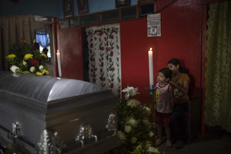 FILE - In this  Sept. 10, 2020 file photo, two of six children of slain journalist Julio Valdivia stand by his casket during a wake inside their home in Tezonapa, Veracruz, Mexico. Valdivia's decapitated body was found five miles from Tezonapa a day earlier and was at least the third reporter killed in the area since 2015. The most authoritative count of homicides in Mexico was published Tuesday, July 27, 2021, and it shows killings remain essentially unchanged in 2020 compared to the previous year. (AP Photo/Felix Marquez, File)