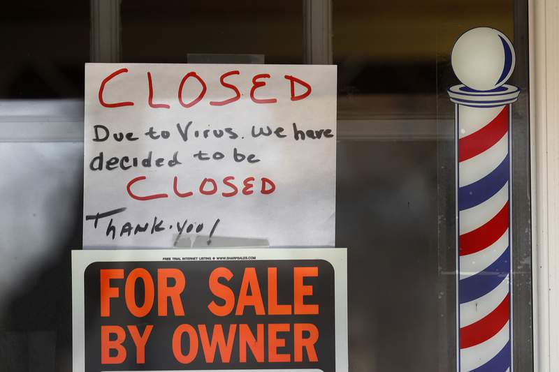 """FILE - In this April 2, 2020 file photo,  """"For Sale By Owner"""" and """"Closed Due to Virus"""" signs are displayed in the window of a store in Grosse Pointe Woods, Mich. Business filings under Chapter 11 of the federal bankruptcy law rose sharply in March, and attorneys who work with struggling companies are seeing signs that more owners are contemplating the possibility of bankruptcy. Government aid my simply be too little too late.   (AP Photo/Paul Sancya, File)"""
