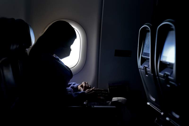 FILE - In this Wednesday, Feb. 3, 2021, file photo, a passenger wears a face mask she travels after take off from Hartsfield-Jackson International Airport in Atlanta. A new study says leaving middle seats open could reduce the risk of airline passengers contracting the virus that causes COVID-19. The study was published Wednesday, April 14, 2021 by researchers from the U.S. Centers for Disease Control and Prevention and Kansas State University. (AP Photo/Charlie Riedel, File)