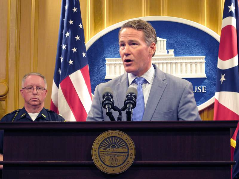 Preble County Sheriff Michael Simpson, left, listens as Ohio Lt. Gov. Jon Husted discusses a proposal to require adding certain warrants to state and federal background check systems, during a news conference Wednesday, Aug. 28, 2019, in Columbus. (AP Photo/Kantele Franko)