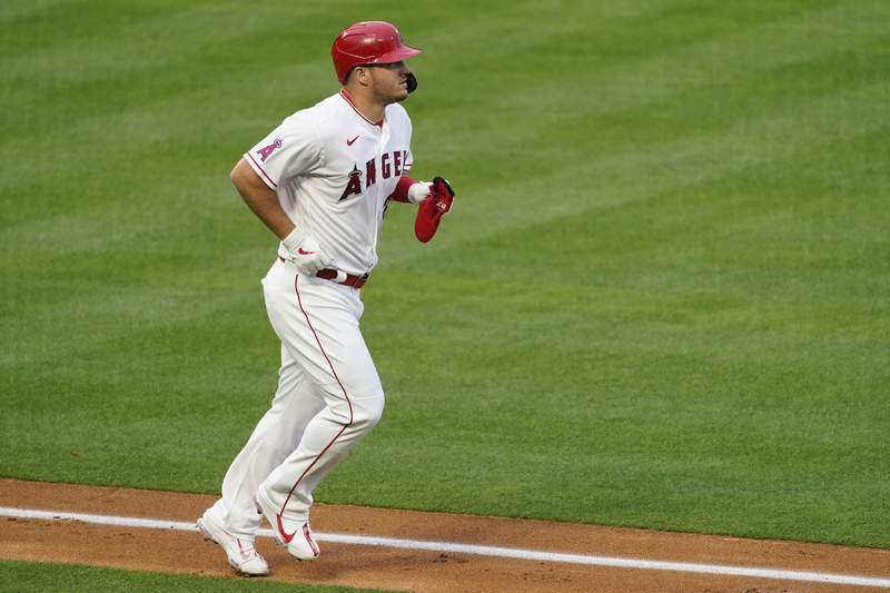 Los Angeles Angels' Mike Trout (27) is walked by Cleveland Indians starting pitcher Sam Hentges during the first inning of a baseball game Monday, May 17, 2021, in Los Angeles. (AP Photo/Ashley Landis)