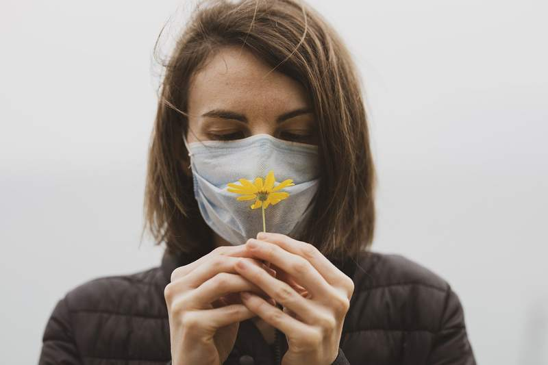 A woman, behind a mask, tries to smell a flower.