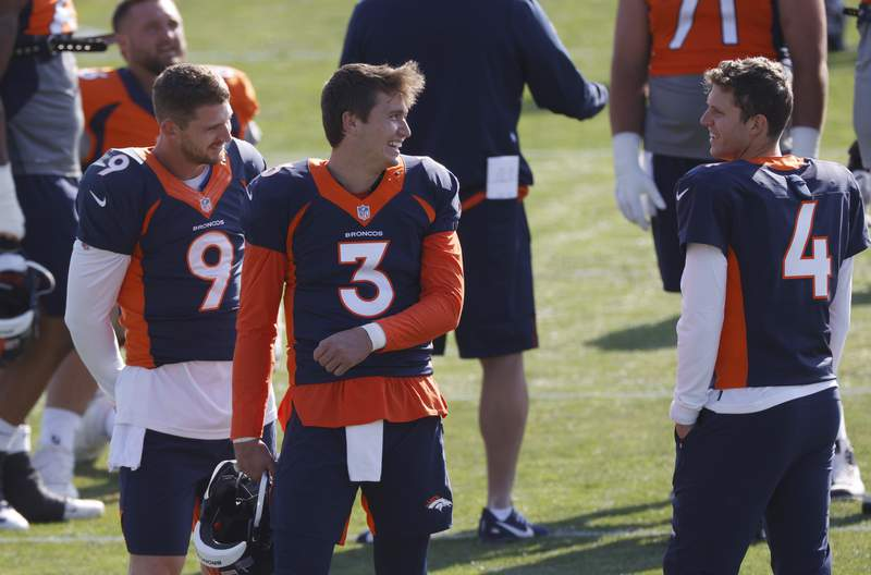 FILE - Denver Broncos quarterback Drew Lock, center, jokes with backup quarterbacks Jeff Driskel, left, and Brett Rypien during an NFL football practice in Englewood, Colo., in this Monday, Aug. 31, 2020, file photo. The Broncos activated three quarterbacksstarter Lock and backups Rypien and Blake Bortlesfrom the COVID-19 list Tuesday, Dec. 1, 2020, to insure that the team will not be without quarterbacks on the roster for the game against the Chiefs in Kansas City on Sunday as the Broncos were last Sunday when hosting the New Orleans Saints. (AP Photo/David Zalubowski, File)